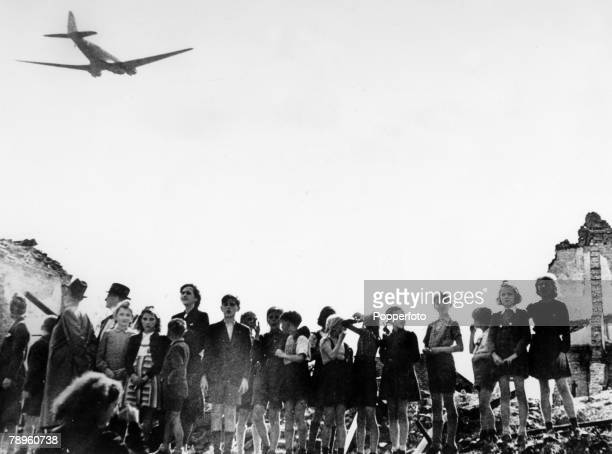 """War and Conflict, Transport, pic: July 1948, Berlin, A C-47 """"Dakota"""" aircraft being flies over a crowd, mainly children to bring supplies to..."""