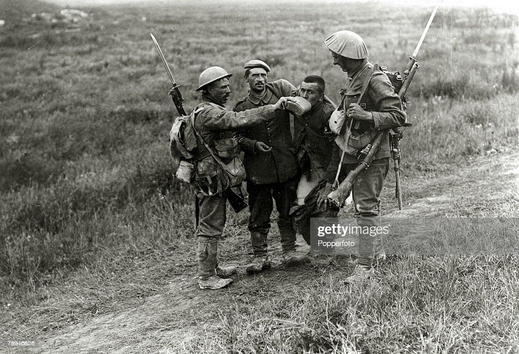 3rd July 1916, Battle of the Somme, France, British troops giving a drink to a wounded German soldier