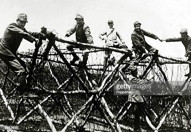 circa 1917 Italian sappers having erected a complicated barbed wire entanglement facing a climbing feat as they attempt to move back to their lines