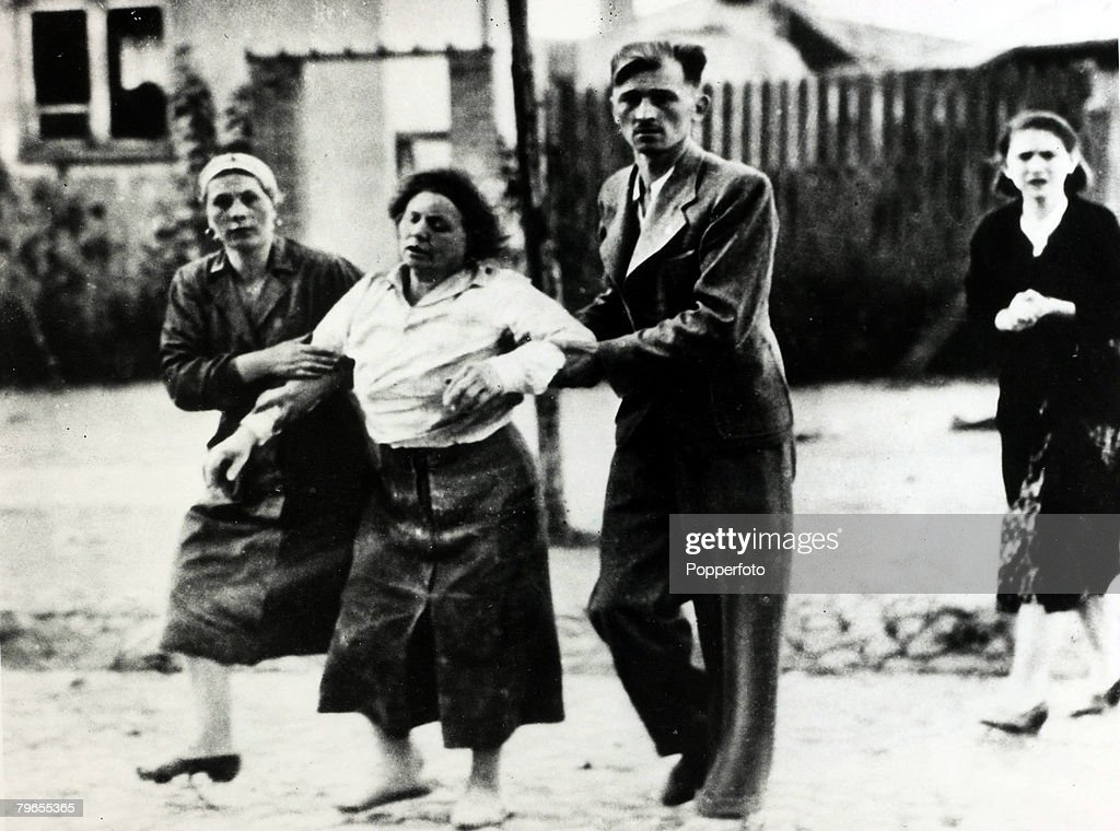 War and Conflict, World War II, Germany invades Poland, pic: September 1939, A Polish woman is helped away after a German bombing raid on a Warsaw suburb