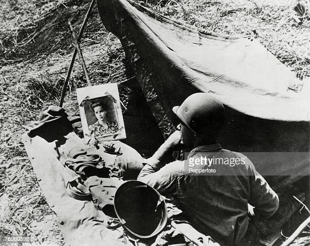 1942 Guadalcanal Solomon Islands A US marine in his foxhole with a grenade alongside a picture of his sweetheart