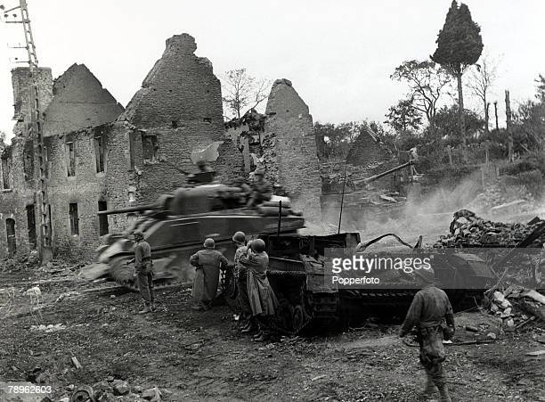 June 1944 An American Sherman tank races past a destroyed German Tiger tankat Sauveur Normandy France during the DDay landings