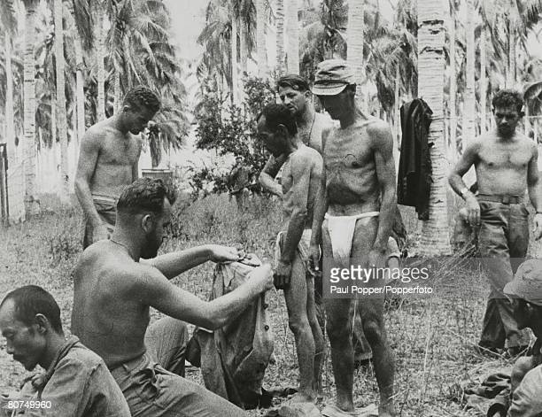 War and Conflict, World War Two, Far East, pic: circa 1942, Japanese prisoners have their clothing checked by their American captors after being...