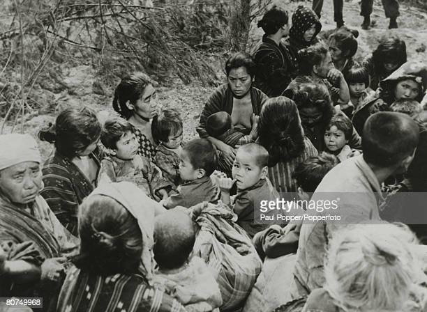War and Conflict, World War Two, Far East, pic: Okinawan women and children huddled together after the American victory in the Battle of Okinawa,...