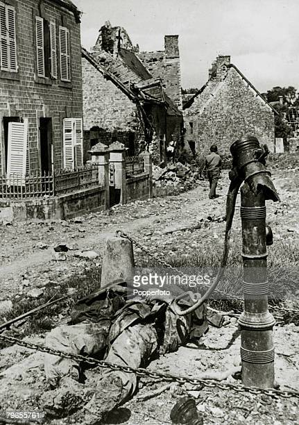 War and Conflict World War Two Invasion of France pic June 1944 The scene at the village water pump in Ste Marcouf Normandy shows a dead American...