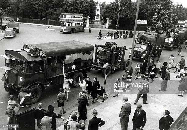 14th June 1944 A convoy of military vehicles passing through the east end of London with women rushing to provide sandwiches and drinks for the...