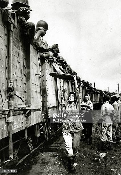 1945 Veteran UStroops from the European War arrive by train in the Philippines in open freight cars and are welcomed with doughnuts delived on a tray