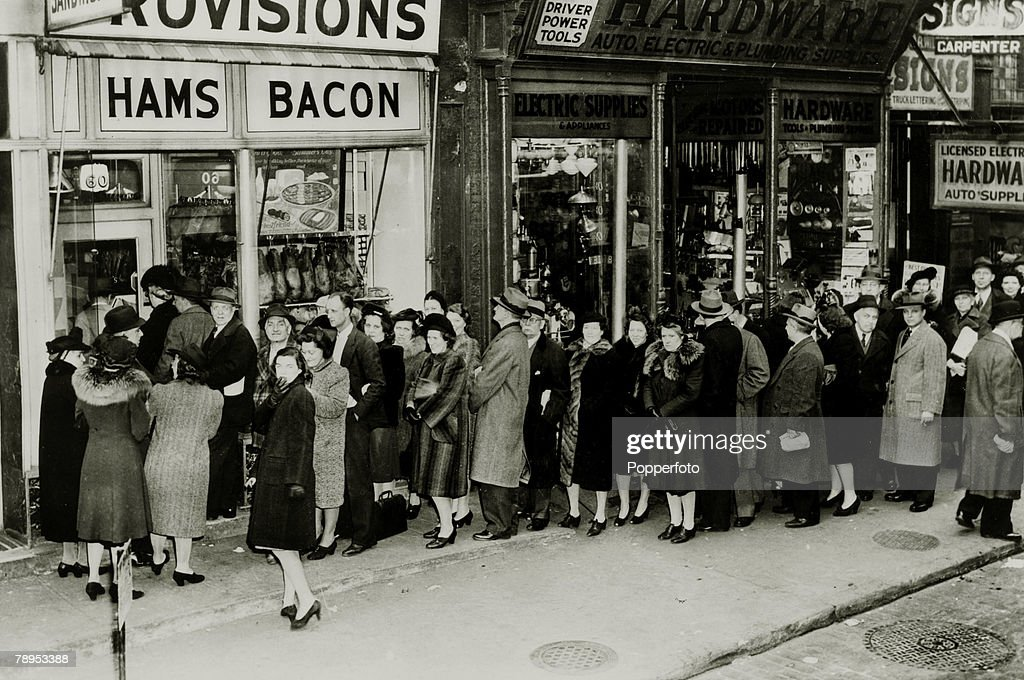 24th March 1943, United States, A New York City queue with people lining up at food stores before rationing starts