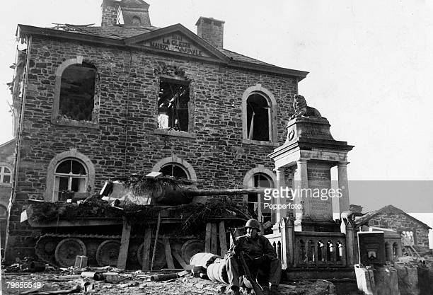 28th December 1944 An American infantrymen stands guard against a knocke out German tank in the Belgian town of La Gleize