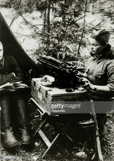 circa 1941 A Russian Army girl typist at work in her makeshift office on the northern front with her tommy gun ready for instant action