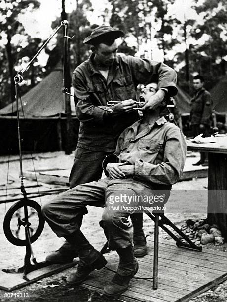 circa 1943 A foot operated drill in operation as a US soldier sits in the dentist's chair the dentist working a makeshift camp in eastern Australia...