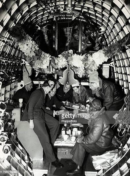 December 1940 The officers and crew of a British Coastal Command Sunderland flying boat decorated for christmas share out the christmas cake before...