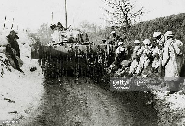 January 1945 A British flail tank passing along a narrow lane near Heinsberg Germany with soldiers wearing snow camouflage suits watching