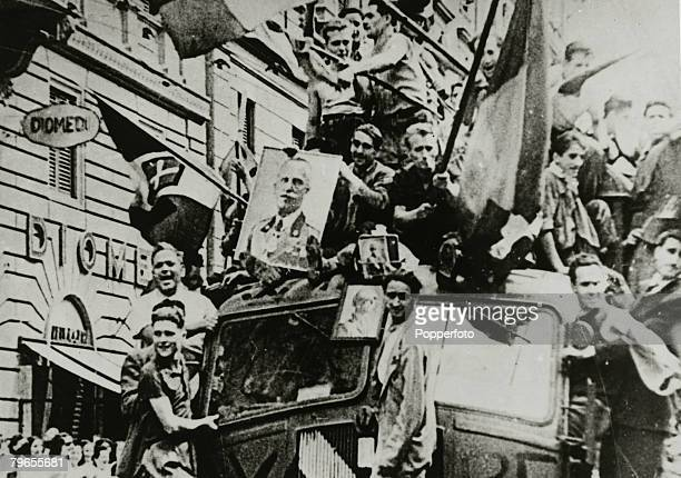 July 1943 Italians out in Rome celebrating the downfall of Benito Mussolini wave Italian flags and show pictures of King Victor Emmanuel