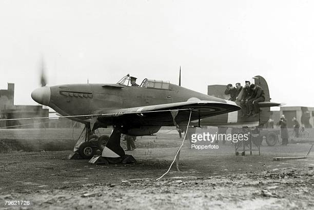 March 1941 An Eagle squadron pilot tests the engines and guns of his Hurricane fighter whilst men sit on the tail to hold the plane down