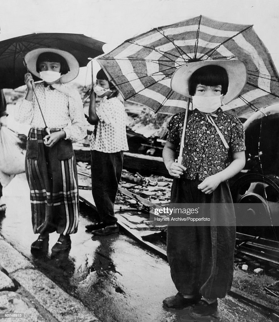 October 1945, Children pictured wearing face masks over nose and mouth to combat the odor of death clinging to the ruins after the Atomic bomb had been dropped on Hiroshima, Japan on 6th August 1945