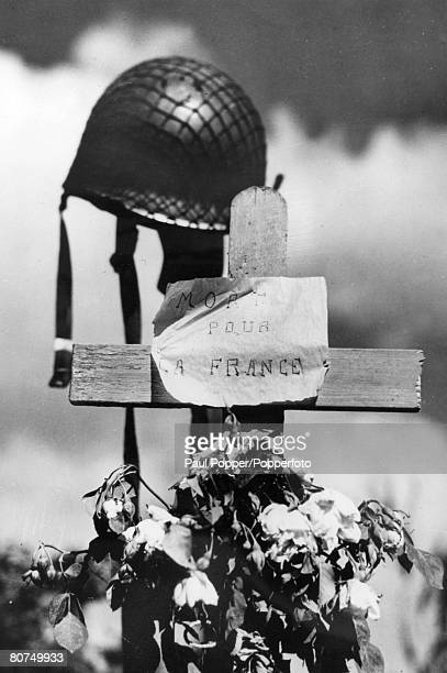 War and Conflict World War Two Remembrance pic 1944 Carentan France French civilians erected this simple cross with flowers alongside the helmet for...