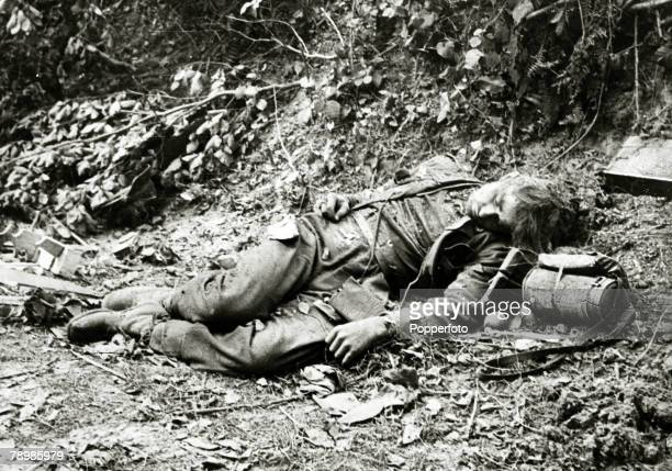 War and Conflict World War Two The Invasion of France pic June 1944 A German infantryman lies dead in a ditch as American troops advance on Cherbourg
