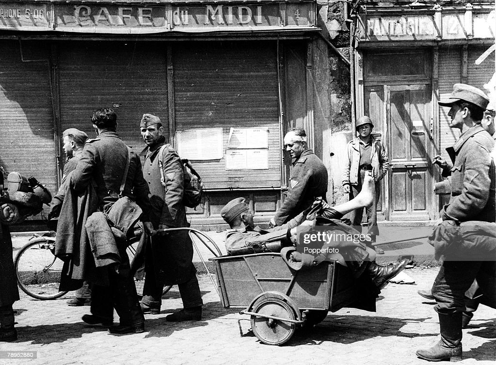 War and Conflict. World War Two. Western Front. pic: June 1944. A wounded German soldier is pulled in a cart as the soldiers become prisoners of war after the fall of Cherbourg, France, to the Americans. : News Photo