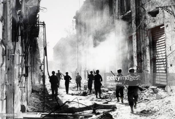 War Conflict World War Two 24th August 1943 Messina Sicily Italy America troops walk down a war ravaged street