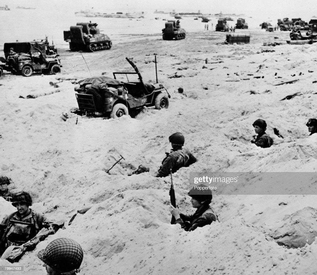 War & Conflict. World War Two. France 6th June 1944. American troops dig in on the Normandy beach head after the D Day Invasion. jeeps and tank units move off the beach. : News Photo