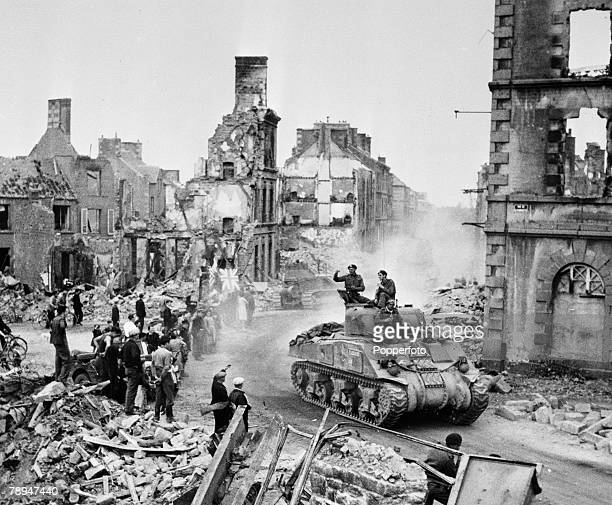 War Conflict World War Two France August American Sherman tanks and troops move through the damaged and bombed town of Flere as they move inland from...