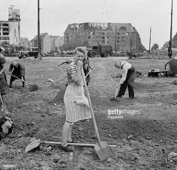 War Conflict World War Two Germany 14th April 1946 A German woman rests on her shovel as she helps to clear bomb damage from the streets of Berlin...