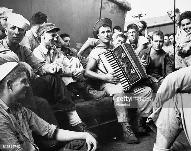 War correspondent Ernie Pyle visits with Marines of the Third Amphibious Forces aboard a transport of the U.S. Pacific Fleet on the way to the...