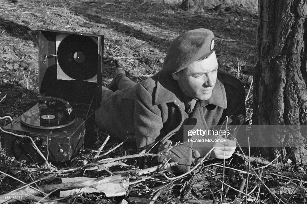 BBC war correspondent Frank Gillard (1909 - 1998) at work in early 1944, during a mock battle to rehearse the reporting of the D-Day landings for BBC radio. He is using a portable disc recorder issued by the BBC War Reporting Unit. Original publication: Picture Post - 1717 - How The BBC Covers The Invasion - pub. 17th June 1944.