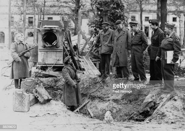 War correspondents are shown the grave where Adolf Hitler's charred body is alleged to have been buried behind the Chancellery in Berlin