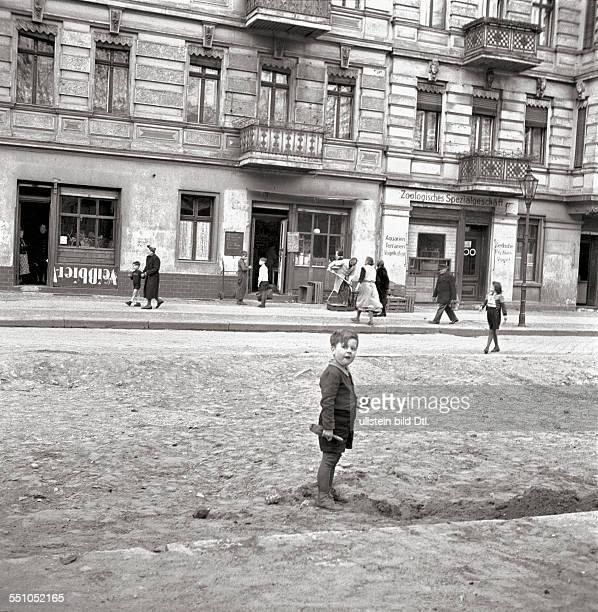 War destructions in Berlin Tiergarten Street view of the Lübecker Straße with the portrait of a small boy Photographer Ernst Hahn