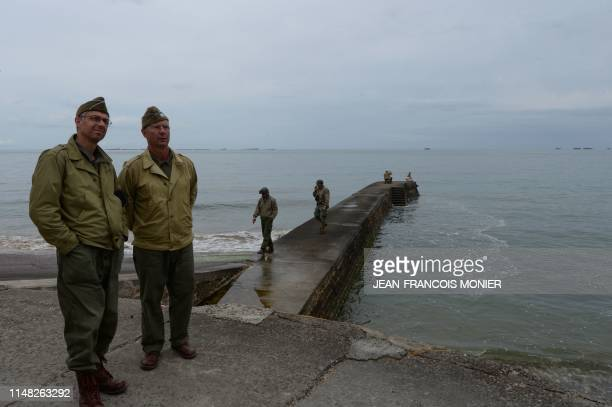 War enthusiasts dressed as WWII soldiers stands on US docks used during the World War II at ArromancheslesBains Normandy northwestern France on June...