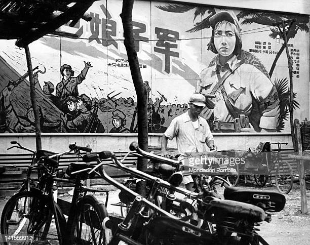 A war film poster appearing behind a bicycle parking stand Beijing 1961