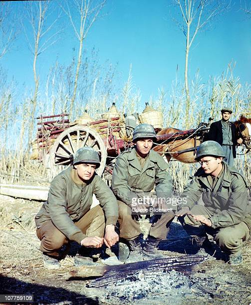 War In Lazio Three United States GIs from the 85thInfantry Division are keeping warm near a fire April 1944 A farmer with his horse is transporting...