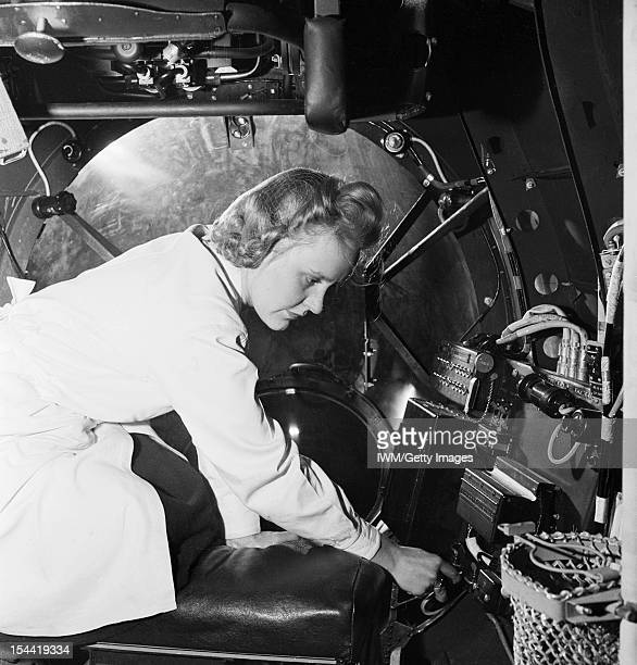 War Industry In Britain 1939-1945, Aircraft construction: A female electrical worker fitting the bomb aimers switch into the half completed fuselage...