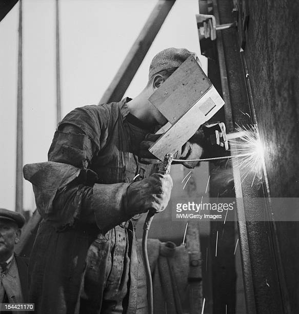 War Industry In Britain 19391945 Shipbuilding A welder wearing a protective mask at work in a British shipyard circa 1943