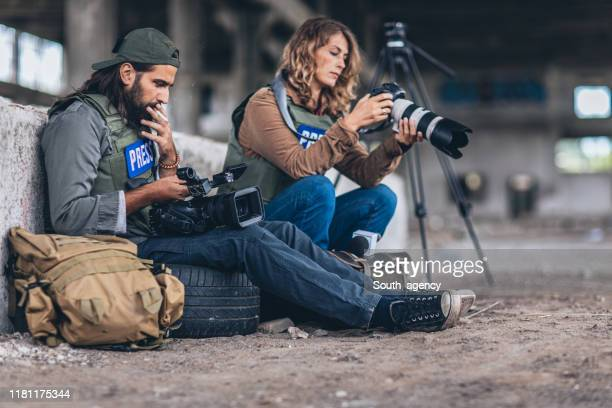 war journalists sitting in war zone - journalist stock pictures, royalty-free photos & images