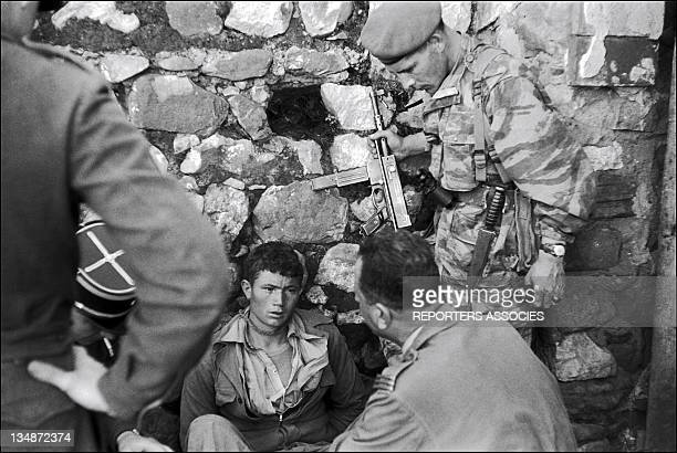 A war prisoner with soldiers during 'Operation Bigeard' in March 1956 when an armed outbreak in SoukAhras South of Constantine region Algeria led to...