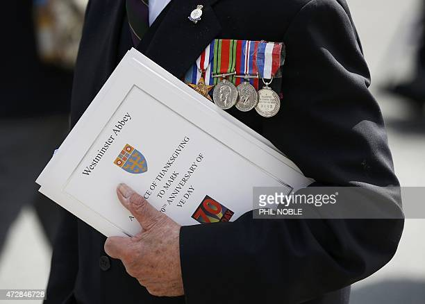A war veteran holds a programme from a service of thanksgiving during an armed forces and veterans' parade to mark the 70th anniversary of VE Day the...