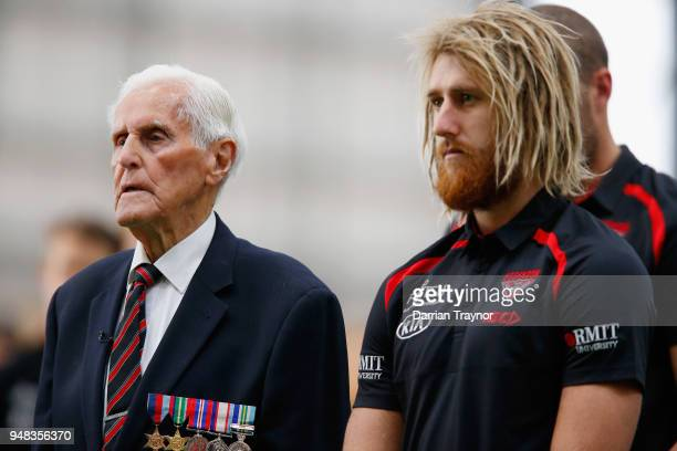 War veteran Jack Jones and Dyson Heppell of the Bombers listen to the 'Last Post' at an ANZAC ceremony before an Essendon Bombers traing session on...