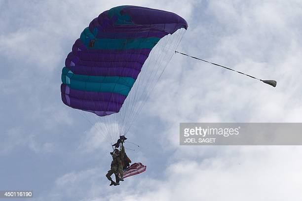 US war veteran Jim 'Pee Wee' Martin prepares to land with a parachute on June 5 2014 over Carentan where he landed 70 years ago when he was a...