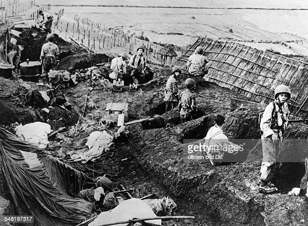 War zone North Vietnam a group of French paratroopers which have dug themselves in an emplacement on the bank of the Black River during retreat...
