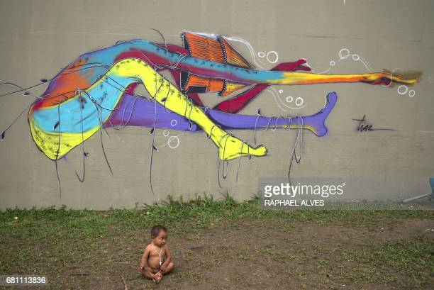 Warao indigenous baby sits on the ground next to a wall of the Ayrton Senna Viaduct where around 400 of them are camped in Manaus Amazonas Brazil on...
