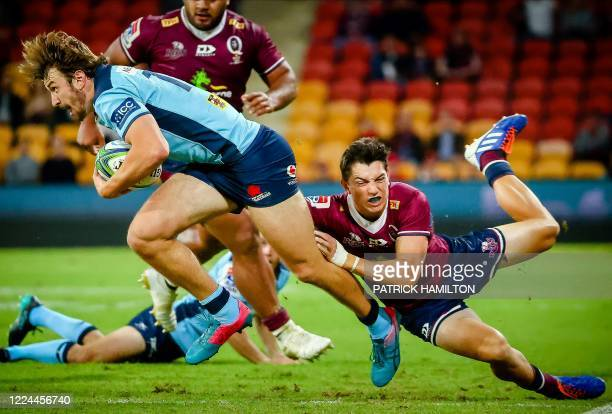 Waratahs' James Ramm is tackled by Reds' Jock Campbell during the Super Rugby match between Australia's Queensland Reds and New South Wales Waratahs...