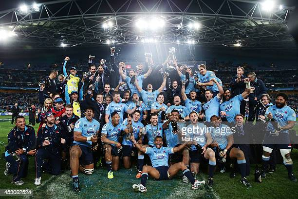 Waratahs players celebrate victory and hold the Super Rugby trophy during the Super Rugby Grand Final match between the Waratahs and the Crusaders at...