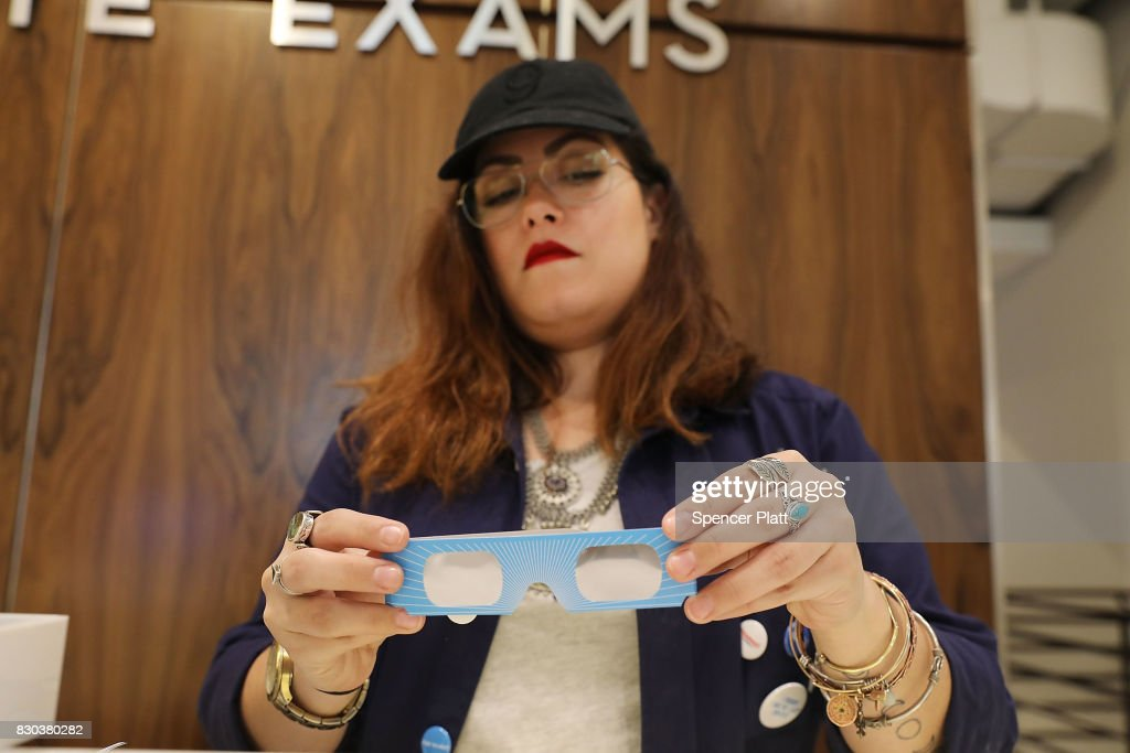 Warby Parker employee Gabi Rivera unfolds a pair of solar eclipse glasses that the eyeglass store is giving out for free on August 11, 2017 in New York City. To view the upcoming total solar eclipse on August 21 eye protection is essential. The designer eyeglass store expects to give out thousands of pairs of the glasses before the event.