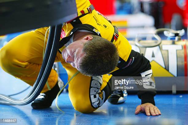 Ward Burton driver of the Bill Davis Racing Dodge Intrepid R/T peers under his car in the garage prior to practice for the EA Sports 500 at Talladega...