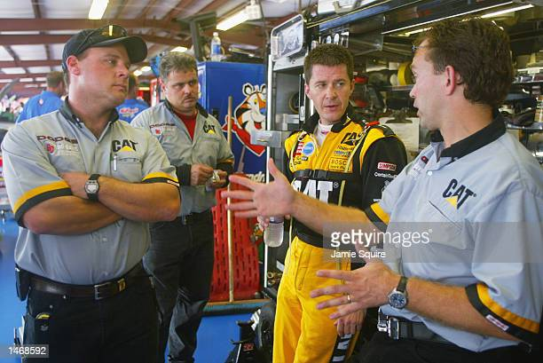 Ward Burton driver of the Bill Davis Racing Dodge Intrepid R/T talks with crew members during practice for the EA Sports 500 at Talladega...