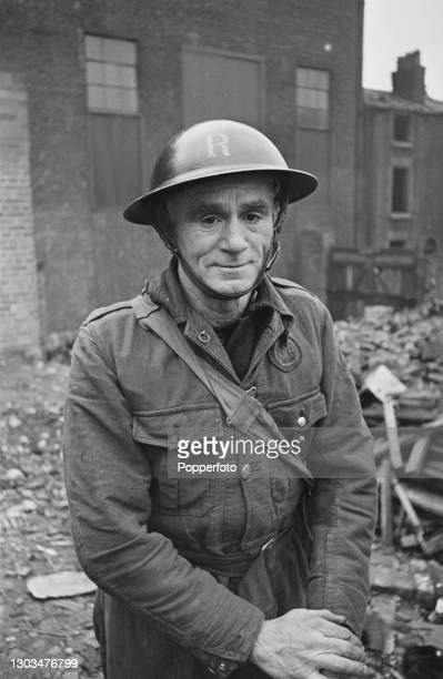 Warden John Hill from an Air Raid rescue squad posed on a bomb site, created by German Luftwaffe air raids in the Liverpool Blitz, in Liverpool,...