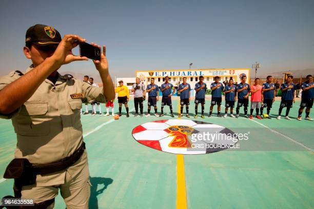 A warden takes a picture as Inmates from Peruvian jails sing the national anthem before the start of their First Interprison World Cup Russia 2018...